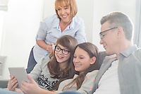 Happy family using tablet PC on sofa at home