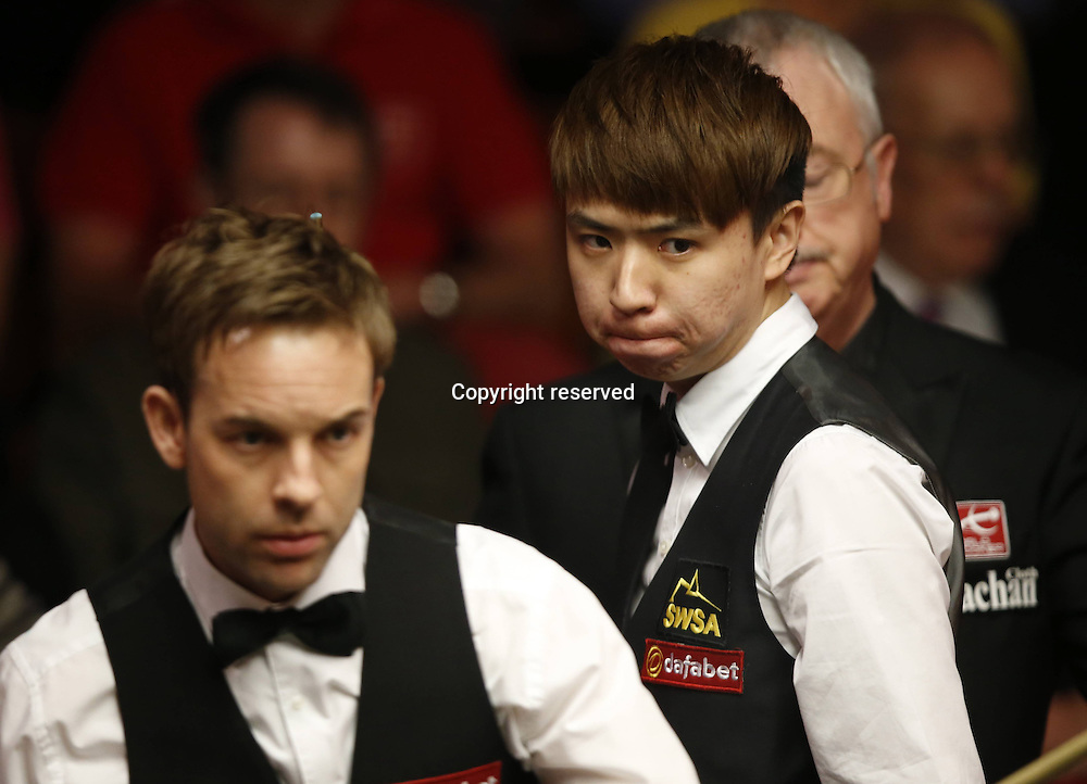 21.04.2014. Sheffield, England.  Xiao Guodong(R) of China looks on during his Round 1 match against  Allister Carter (Eng)on Day 2 of World Snooker Championship at the Crucible Theatre in Sheffeild, Britain, April 20, 2014. Xiao lost 8-10.