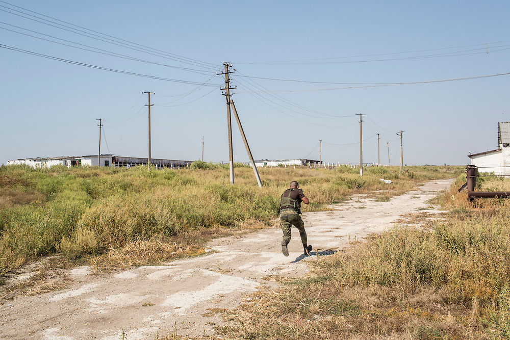 CHERMALYK, UKRAINE - AUGUST 29, 2015: A Ukrainian soldier runs in an area of a local farm suspected of being targetable by snipers in Chermalyk, Ukraine. Two days earlier, the farm was shelled by rebels based just across the nearby Kalmius River, with a level of skill that the soldiers felt indicated they were being targeted by professional Russian soldiers rather than rebel irregulars. CREDIT: Brendan Hoffman for The New York Times