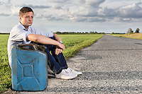 Full length of young man with empty gas can sitting by road