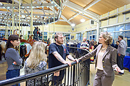 Garden City, New York, USA. March 9, 2019.  L-R, Maranda Mele, carousel operators BETH ORBERG and her son ANDREW OBERGH, and Nassau County Executive LAURA CURRAN talk at railing around Nunley's Carousel, during Unveiling Ceremony of mural of a Nunley's Carousel horse.  Event was held at historic Nunley's Carousel in its Pavilion on Museum Row on Long Island.