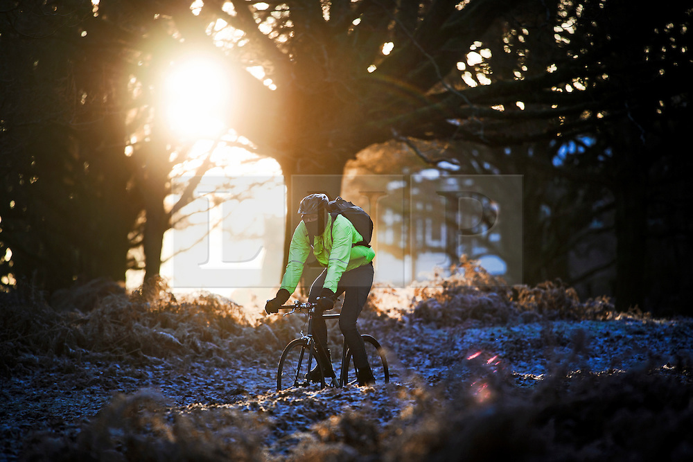 © Licensed to London News Pictures. 03/01/2017. London, UK. A man cycles through a frost covered landscape in Richmond Park in London as temperatures in the capital drop below zero. . Photo credit: Ben Cawthra/LNP