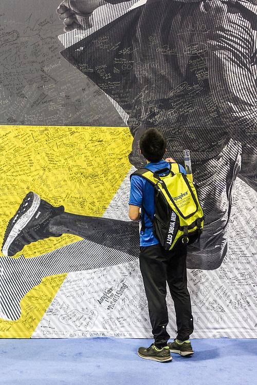 Boston Marathon: Expo, attendee signs mural on wall