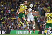 Norwich City striker (on loan from Sheffield Wednesday) Jordan Rhodes (11) heads the ball  under  pressure from Leeds United defender Luke Ayling (2) during the EFL Sky Bet Championship match between Norwich City and Leeds United at Carrow Road, Norwich, England on 25 August 2018.