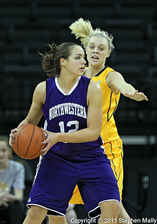 December 30, 2011: Northwestern Wildcats guard Allison Mocchi (12) looks to pass as Iowa Hawkeyes guard Jaime Printy (24) defends during the NCAA women's basketball game between the Northwestern Wildcats and the Iowa Hawkeyes at Carver-Hawkeye Arena in Iowa City, Iowa on Wednesday, December 30, 2011.