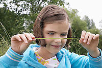Girl (7-9) examining caterpillar on grass in field