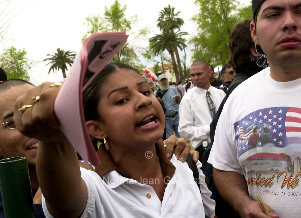 """An unidentified teen shouts at counter protestors questioning if they """"have papers"""" as the counter protestors prepare to burn the Mexican flag at a protest of immigration legislation attended by about 15,000 on April 10, 2006, at Armory Park in Tucson, Arizona."""