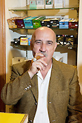 Portrait of mature tobacco store owner smoking cigar