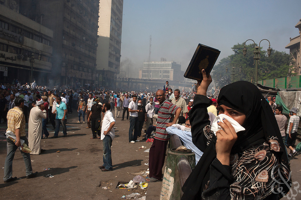 """An Egyptian woman holds a Koran aloft amid tear gas and smoke as intense street clashes take nearby around Ramsis Square during the August 16, 2014 """"Day of Rage"""" protests in Cairo, Egypt."""