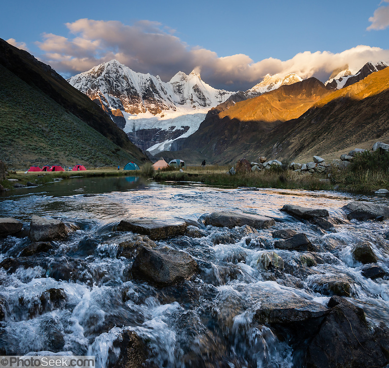 At Incahuain campground, Rio Jahuacocha flows from the melting glaciers of Mount Jirishanca (Icy Beak of the Hummingbird, 6126 m or 20,098 feet) at sunset. Day 8 of 9 days trekking around the Cordillera Huayhuash in the Andes Mountains, one day's walk from LLamac, Peru, South America. This panorama was stitched from 2 overlapping photos.