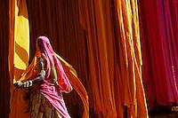 Inde, Rajasthan, Usine de Sari, Da Adan, 60 ans. Les tissus sechent en plein air. Ramassage des tissus secs par des femmes et des enfants avant le repassage. Les tissus pendent sur des barres de bambou. Les rouleaux de tissus mesurent environ 800 m de long. . // India, Rajasthan, Sari Factory, Da Adan, 60 old. Textile are dried in the open air. Collecting of dry textile  are folded by women and children. The textiles are hung to dry on bamboo rods. The long bands of textiles are about 800 metre in length.