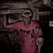 Brasile, Amazzonia, garimpo de Juma. Le miniere a cielo aperto del garimpo de Juma, dove la vita dei minatori scorre tra pericolo per un lavoro al limite e deforestazione incontrollata. Aspettando di trovare l'oro che cambi la loro vita. In questa foto un minatore all'interno ad uno degli innumerevoli e pericolosi tunnel. Brazil, Amazonia, garimpo de Juma. The open pit mines of garimpo de Juma, where the miners work flows between danger and uncontrolled deforestation. Waiting to find the gold that changes their lives. In this picture a miner in one of the many and dangerous tunnel.