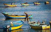 A Fishermen walks betweem skiffs along the waterfront in Gaza City.