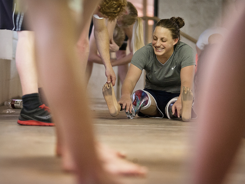 Lehi High School swimmer Amy Chapman laughs as coach Chad Reimschussel reaches for her prosthetic toes during dry-land practice at the Lehi Legacy Center, Tuesday, Dec. 18, 2012. Chapman, 17, was born with fibular hemimelia and had both legs amputated when she was 13 months old.