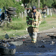 "Acton, TX / 2005 - Robert Alonzo of the Edinburg Fire Department surveys the damage a fatal crash between a propane truck and asphalt ""hot mix"" tanker early Tuesday morning at the intersection of FM 681 and FM 1925 in Acton. - Photo by Mike Roy/The Monitor"