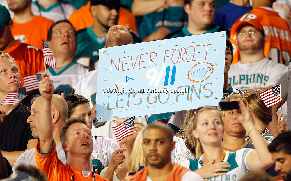 "Miami Dolphins fans hold up a sign stating ""Never Forget 9/11""  during the playing of the National Anthem at the NFL week 1 football game against the New England Patriots on Monday, September 12, 2011 in Miami Gardens, Florida. The Patriots won the game 38-24. ©Paul Anthony Spinelli"