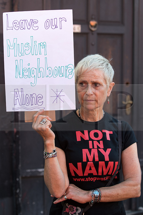 """© Licensed to London News Pictures. 19/06/2017. London, UK. A local resident protests at the scene with a placard reading """" Leave our Muslim neighbours alone """" . One man is known to be dead and several inured after a hired van was driven in to people on Whadcoat Street in Finsbury Park in North London after late night prayers at a nearby mosque . Photo credit: Joel Goodman/LNP"""