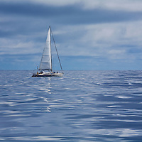 A single handed sailboat motors through dead flat calm seas in the north Atlantic Ocean due west of the Azores Atlantic