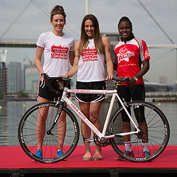 © Licensed to London News Pictures. 27/07/2013. London, UK. Jade Jones, Melanie C and Nicola Adams (left to right) pose with a bicycle at the London Triathlon 2013 at the ExCel centre in Royal Victoria Dock in East London. Photo credit : Vickie Flores/LNP