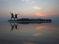 A joyful couple jump in the air, Ko Kut, Thailand, Southeast Asia