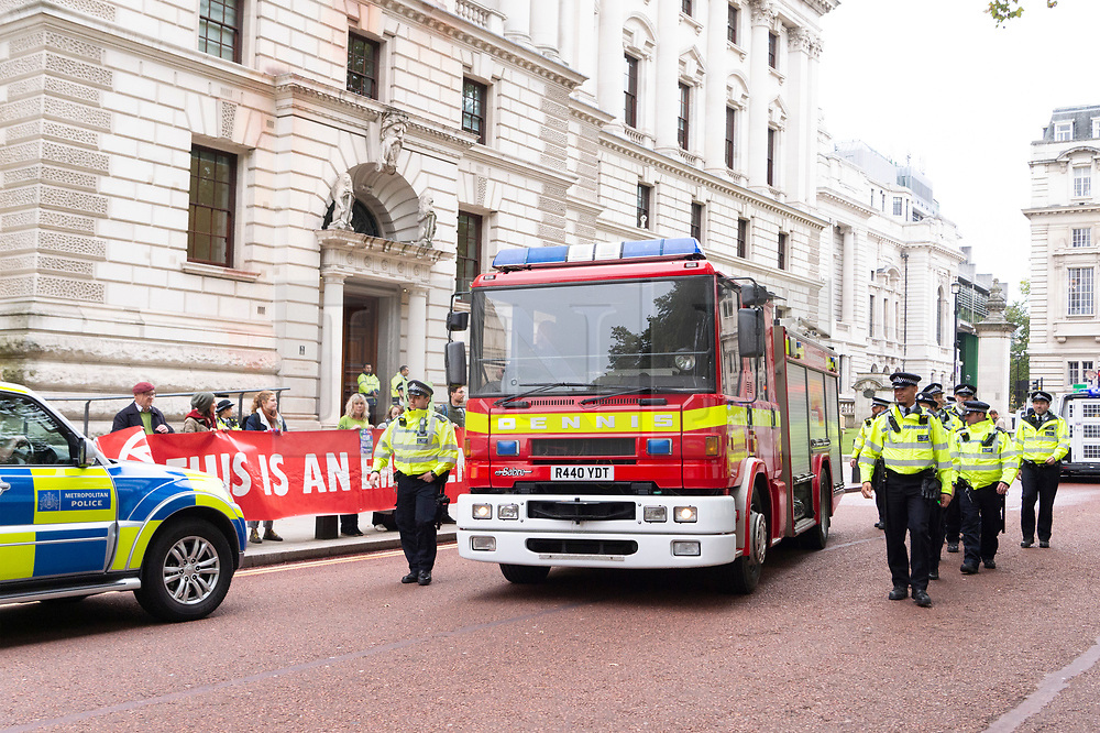 "© Licensed to London News Pictures. 03/10/2019. London, UK. Police officers escort a fire engine used by Extinction Rebellion protesters to stage a protest after spraying the front of the Treasury building with fake blood. Extinction Rebellion said it wanted to highlight the ""inconsistency between the UK Government's insistence that the UK is a world leader in tackling climate breakdown, while pouring vast sums of money into fossil exploration and carbon-intensive projects"". Photo credit: Ray Tang/LNP"