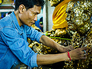 29 MAY 2018 - BANGKOK, THAILAND: A man makes merit by putting gold leaf on a statue of the Buddha during Vesak observances at Wat Hua Lamphong in Bangkok. Vesak is the Buddha's birthday, and one of the most important holy days in the Theravada Buddhist religion. Many Thais visit their local temples for Vesak and rededicate themselves to the Dharma, listen to talks about Buddhism and make merit by bringing flowers to the temple.       PHOTO BY JACK KURTZ
