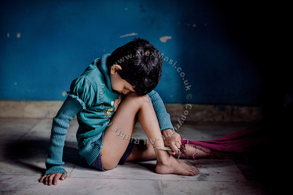 Rachi, 7, a disabled girl affected by microcephaly and myoclonic epilepsy, is trying to unknot a cord to her ankle, used by her mother Jyoti Yadav, 34, a '1984 Gas Survivor', to keep her from wandering off alone, and being at risk of abuse and danger, while inside their home in Bhopal, central India.