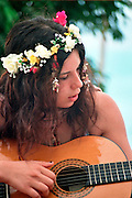 A young flower girl playing the guitar