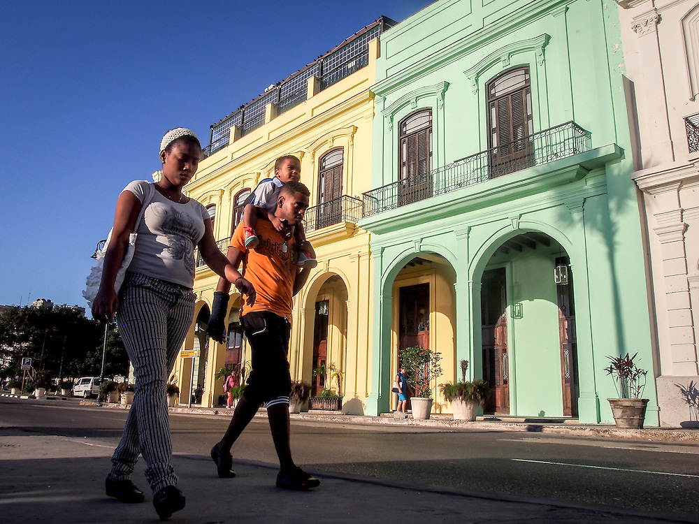 A Mother and Father take their boy to school in the early morning light as Havana wakes up. Many houses and commercial buildings are slowly being restored throught Havana and most of them are painted in beautiful vibrant colours. Travel images from Havana Cuba. Pictures by Chris Pavlich Photography.