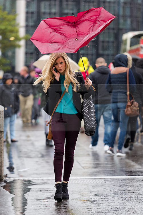 © Licensed to London News Pictures. 14/05/2015. London, UK. A woman struggles to control her umbrella as she talks on her mobile phone during heavy rain and wet and windy weather in Westminster, central London today. Photo credit : Vickie Flores/LNP