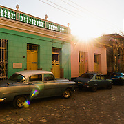 Cobblestoned street in Trinidad, Cuba with vintage cars