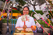 20 OCTOBER 2012 - BANGKOK, THAILAND:  A woman leaves a cash donations for Buddhist temples in Thailand's south. More than 2,600 Buddhist Monks from across Bangkok and thousands of devout Thai Buddhists attended the mass alms giving ceremony in Benjasiri Park in Bangkok Saturday morning. The ceremony was to raise food and cash donations for Buddhist temples in Thailand's violence plagued southern provinces. Because of an ongoing long running insurgency by Muslim separatists many Buddhist monks in Pattani, Narathiwat and Yala, Thailand's three Muslim majority provinces, can't leave their temples without military escorts. Monks have been targeted by Muslim extremists because, in the view of the extremists, they represent the Thai state.       PHOTO BY JACK KURTZ