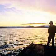 Man on a dock at sunrise. Moosehead Lake. Rockwood, Maine
