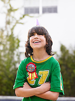 Portrait of boy (10-12) laughing arms crossed