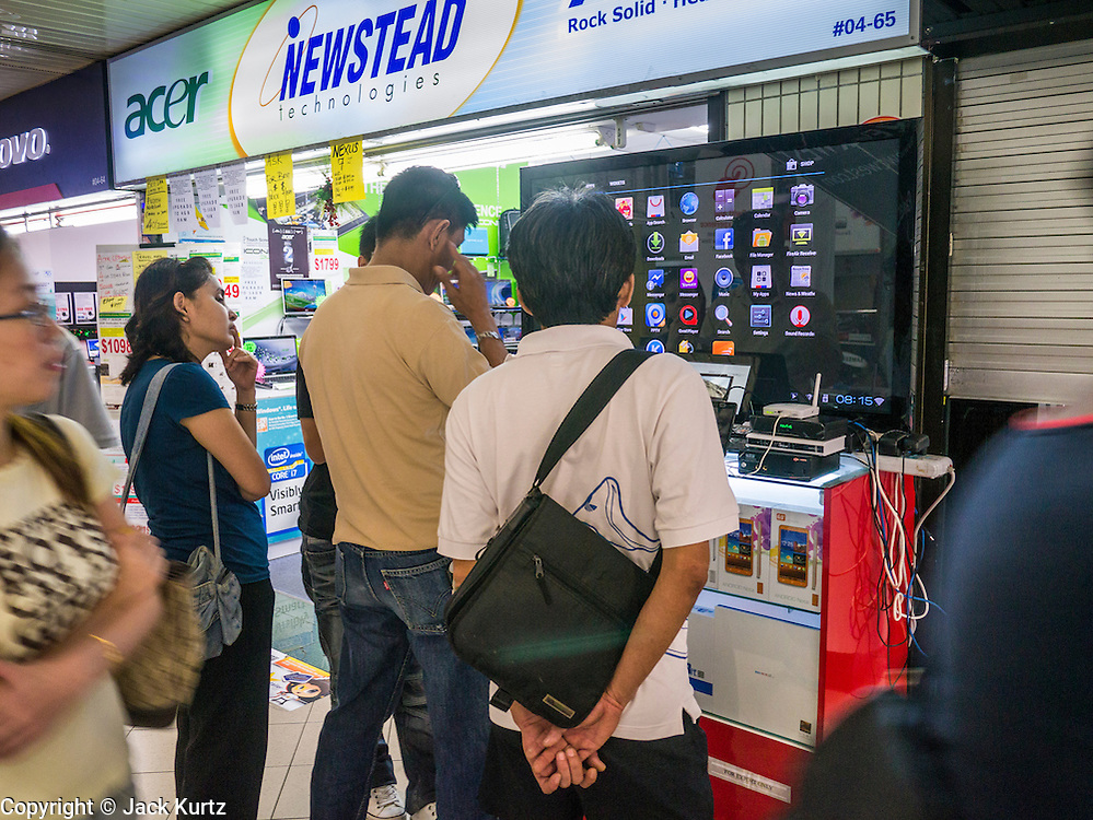 23 DECEMBER 2012 - SINGAPORE, SINGAPORE: Shoppers look at a television connected to the internet at a shop in Sim Lim Square. Sim Lim Square, commonly referred to as SLS, is a large retail complex that offers a wide variety of electronic goods and services ranging from DVDs, cameras, phones, video cameras, and computer parts and servicing. SLS is opposite the historic  Little India district and close to one of the earliest HDB (Singapore housing agency) developments. SLS is accessible via MRT at Bugis or Little India.   PHOTO BY JACK KURTZ