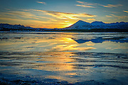 A sunset reflected in the frozen waters of the Olds River. Kodiak Island, Alaska.