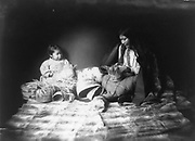 Indian woman and child weaving baskets.