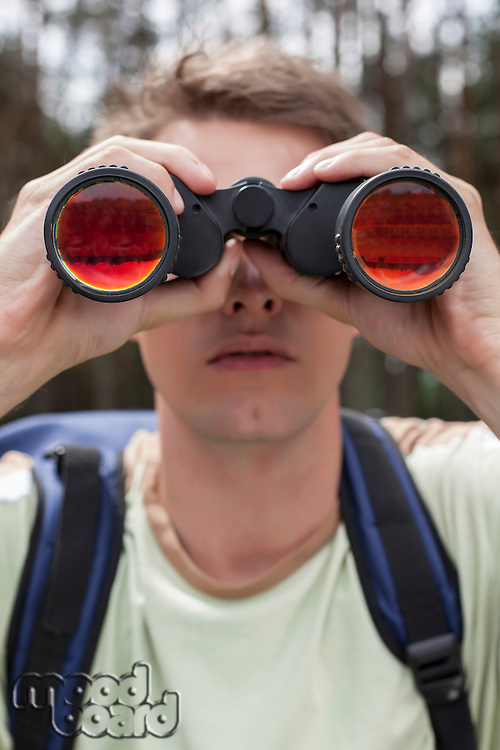Close-up of young man looking through binoculars in forest