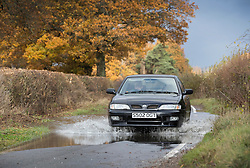 © Licensed to London News Pictures. 22/11/2016. Lingfield, UK. A car splashes though surface water near Lingfield. Parts of the United Kingdom are still experiencing flooding after storm Angus. Photo credit: Peter Macdiarmid/LNP
