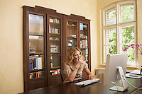 Young woman yawning over computer in living room