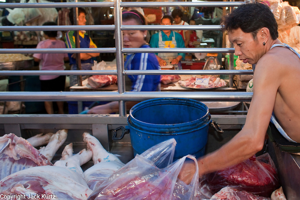 Sept. 23, 2009 -- BANGKOK, THAILAND: A man delivers pig's blood to stalls in Khlong Toey Market in Bangkok, Thailand. Khlong Toey Market is the largest market in Bangkok. Vendors sell everything from meat and fish to fruit and vegetables. They also sell clothes and dry goods in the market. Many working class Thais shop for food everyday because they don't have refrigerators and can't store food at home.   Photo by Jack Kurtz
