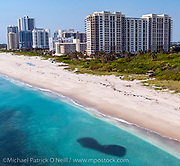 The deserted beach in Singer Island, FL during the COVID 19 lockdown, when beaches in the state were closed to the public to minimize the spread of the Corona Virus. The dark spot on the bottom of the image is a school of glass minnows.