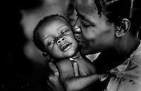 A mother kisses her son in the hospital bed in the Port-au-Prince slum of Cite Soleil. Although he was being treated for malnutrition and protein deficiency, doctors fear he may have AIDS.