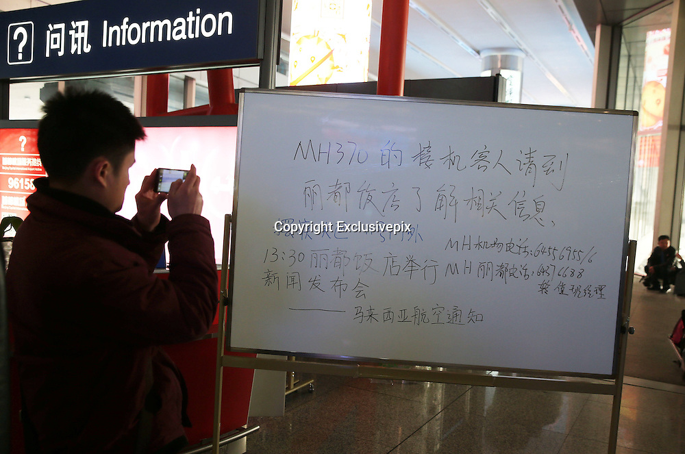 BEIJING, CHINA - MARCH 8: (CHINA OUT)<br /> <br /> Malaysia Airlines Disaster<br /> <br /> A man takes a photo of a notice aimed at relatives of passengers onboard Malaysia Airlines flight MH370 to gather at a hotel at the Beijing Capital International Airport on March 8, 2014, in Beijing, China. Malaysia Airlines Flight MH370 from Kuala Lumpur to Beijing and carrying 239 onboard was reported missing after the crew failed to check in as scheduled while flying over the sea between Malaysia and Ho Chi Minh City in Vietnam, according to published reports.<br /> ©Exclusivepix