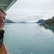 George Twarski films glaciers from his private balcony on board the Norwegian Pearl, a cruise ship of Norwegian Cruise Line at Glacier Bay National Park.  Photography by Jose More<br />  MR Model Release