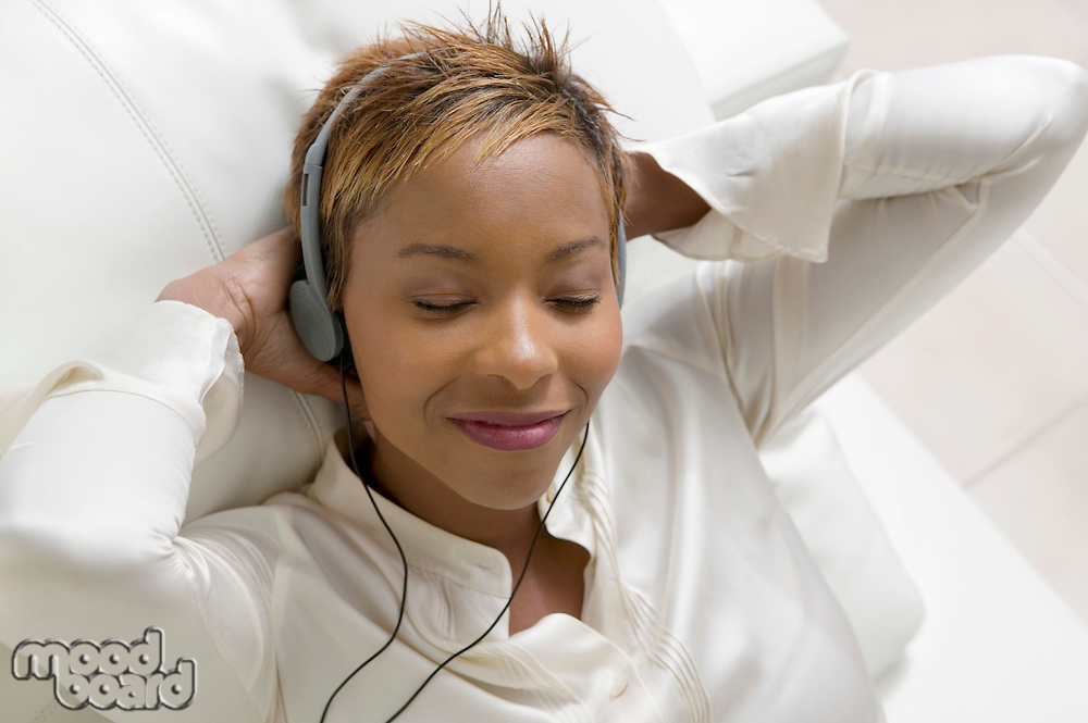 Woman lying on sofa Listening to Music on portable CD player close up overhead view