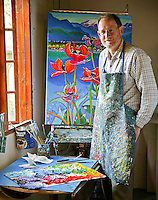 Local Comox Valley artist, Brian Scott, known for his bright, colorful canvas is portrayed in his equally colorful smock in his Black Creek studio.  Black Creek, Vancouver Island, British Columbia, Canada.
