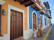 Colorful houses on cobblestone street in Old San Juan, Puerto Rico. Mother and daughter wearing traditional clothes for events commemorating April 1797!