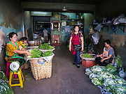 17 MAY 2013 - BANGKOK, THAILAND:  Vendors selling fresh vegetables in a shophouse in the flower market in Bangkok.  The Bangkok Flower Market (Pak Klong Talad) is the biggest wholesale and retail fresh flower market in Bangkok. It is also one of the largest fresh fruit and produce markets in the city. The market is located in the old part of the city, south of Wat Po (Temple of the Reclining Buddha) and the Grand Palace.   PHOTO BY JACK KURTZ