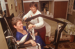 Carer using mechanical hoist to transfer woman with disability from wheelchair,